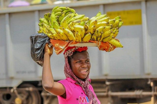 une femme portant un régime de bananes